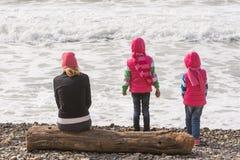 Deux filles et une fille sur la plage se reposant sur un rondin et examinant la distance Photos libres de droits