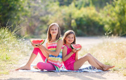 Deux filles et une pastèque rouge juteuse Images stock