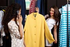 Deux filles faisant des achats dans le mail On parlant du téléphone Images stock