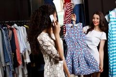 Deux filles faisant des achats dans le mail On parlant du téléphone Photo stock