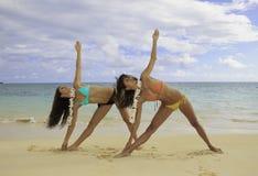 Deux filles faisant le yoga à la plage Photo stock