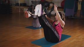 Deux filles font des exercices de Pilates pour les bras et les épaules avec un anneau de fitnes clips vidéos