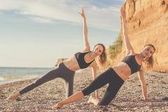 Deux filles font des pilates sur la plage Image stock