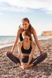 Deux filles font l'étirage sur la plage Photographie stock libre de droits