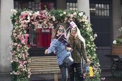 Deux filles font le selfie avec un auto-bâton autour de la voûte des roses artificielles au jardin de Covent Image libre de droits