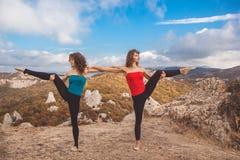 Deux filles font le yoga d'acro dans le paysage de montagnes Image stock