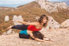Deux filles font le yoga dans le paysage de montagnes Images stock