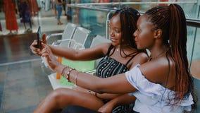 Deux filles font Selfie avec le téléphone après l'achat clips vidéos