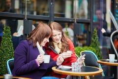 Deux filles gaies buvant du café dans un café parisien de rue Photographie stock