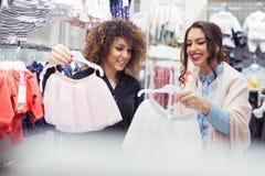 Deux filles gaies faisant des emplettes pour des vêtements Photo stock