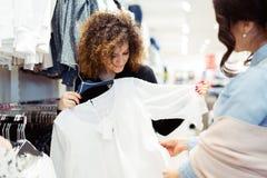Deux filles gaies faisant des emplettes pour des vêtements Photos stock