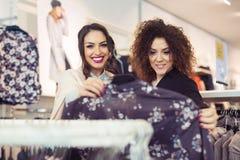 Deux filles gaies faisant des emplettes pour des vêtements Image stock