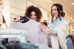 Deux filles gaies faisant des emplettes pour des vêtements Image libre de droits