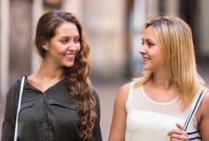 Deux filles gaies marchant dans la ville Images stock