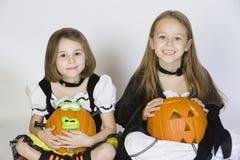Deux filles habillées dans des costumes de Halloween tenant des Jack-O-lanternes Photos stock