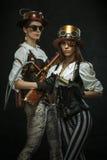 Deux filles habillées dans le style du steampunk avec des bras photo stock