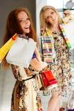 Deux filles heureuses attirantes faisant des emplettes à l'extérieur Image stock