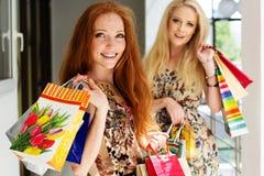 Deux filles heureuses attirantes faisant des emplettes à l'extérieur Photo stock