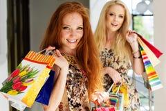 Deux filles heureuses attirantes faisant des emplettes à l'extérieur Photos stock
