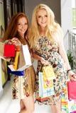 Deux filles heureuses attirantes faisant des emplettes à l'extérieur Photographie stock