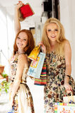 Deux filles heureuses attirantes faisant des emplettes à l'extérieur Image libre de droits