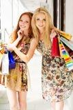 Deux filles heureuses attirantes faisant des emplettes à l'extérieur Photo libre de droits