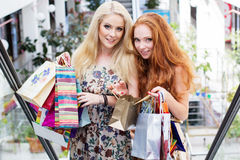 Deux filles heureuses attirantes faisant des emplettes à l'extérieur Photographie stock libre de droits