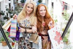 Deux filles heureuses attirantes faisant des emplettes à l'extérieur Images libres de droits
