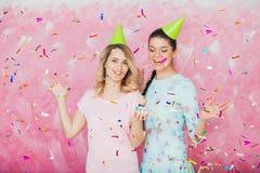 Deux filles heureuses célèbrent la fête d'anniversaire avec les confettis a de petit gâteau Photo stock