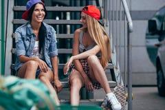 Deux filles heureuses causant sur des escaliers Photographie stock libre de droits