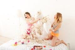Deux filles heureuses combattant avec des oreillers Photographie stock