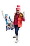 Deux filles heureuses dans des vêtements d'hiver sur le traîneau Photographie stock libre de droits