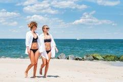 Deux filles heureuses dans le bikini sur la plage Meilleurs amis marchant sur la plage Image libre de droits