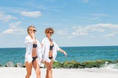 Deux filles heureuses dans le bikini sur la plage Meilleurs amis marchant sur la plage Images stock
