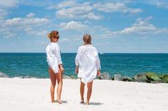 Deux filles heureuses dans le bikini sur la plage Meilleurs amis marchant sur la plage Image stock