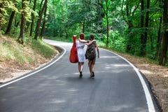 Deux filles heureuses dans une route faisant de l'auto-stop avec le sac à dos et la guitare Photographie stock