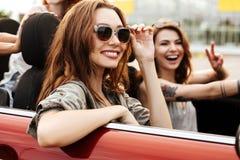 Deux filles heureuses de sourire dans des lunettes de soleil ayant le tour d'amusement Photos stock