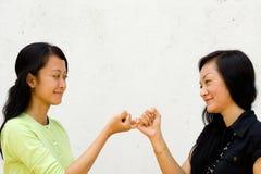 Deux filles heureuses effectuent la paix entre eux Image stock