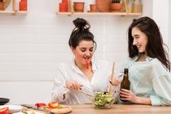 Deux filles heureuses faisant cuire la salade fraîche ensemble photographie stock