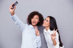 Deux filles heureuses faisant la photo de selfie sur le smartphone Images stock