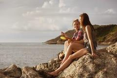 Deux filles heureuses parlent à la plage de coucher du soleil Photo stock