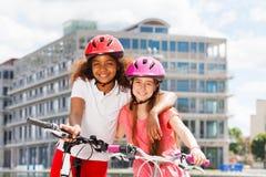 Deux filles heureuses pendant la bicyclette montent dans la ville d'été Images libres de droits