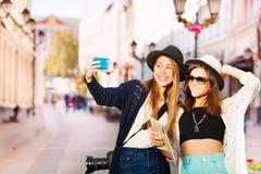 Deux filles heureuses prenant des selfies avec le téléphone portable Photo stock