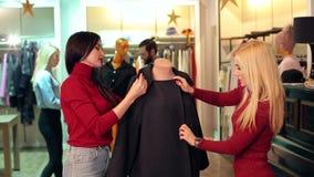 Deux filles heureuses regardant des vêtements sur un mannequin dans un magasin d'habillement clips vidéos