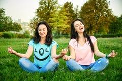 Deux filles heureuses s'asseyent sur l'herbe images libres de droits