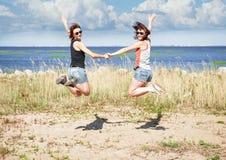 Deux filles heureuses sautant sur la plage en été Photographie stock libre de droits