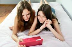 Deux filles heureuses se situant dans le lit et regardant le comprimé horizont Photo stock