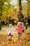 Deux filles jetant des feuilles en parc d'automne Photographie stock