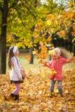 Deux filles jetant des feuilles en parc d'automne Photos stock