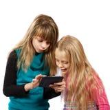Deux filles jouant avec le PC de comprimé Photo stock